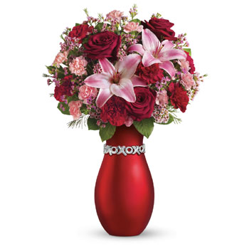Surprise your Valentine with luscious red roses and pink lilies presented in the XOXO keepsake vase. You'll get a very warm rece