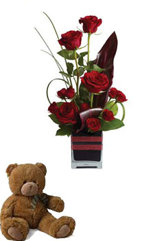 Roses, the traditional flower of love, receive a modern twist in this imaginative arrangement and a teddy.